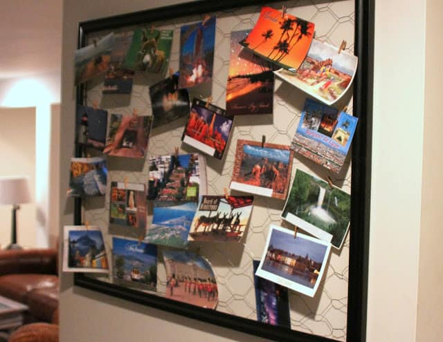 An empty picture frame is repurposed as a postcard display.
