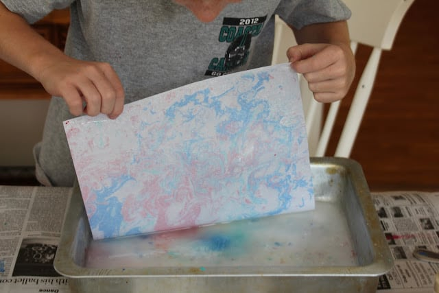 Marble painting with acrylic paints poured onto the surface of water.