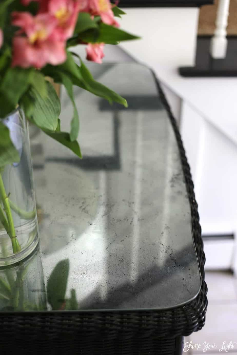 A glass tabletop is given a DIY mercury glass effect with spray paint and a vinegar and water mixture for a beautiful mottled finish.