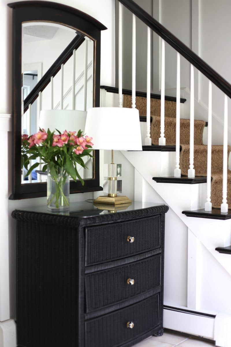 A dresser used in a foyer for extra storage, with a DIY mercury glass tabletop.