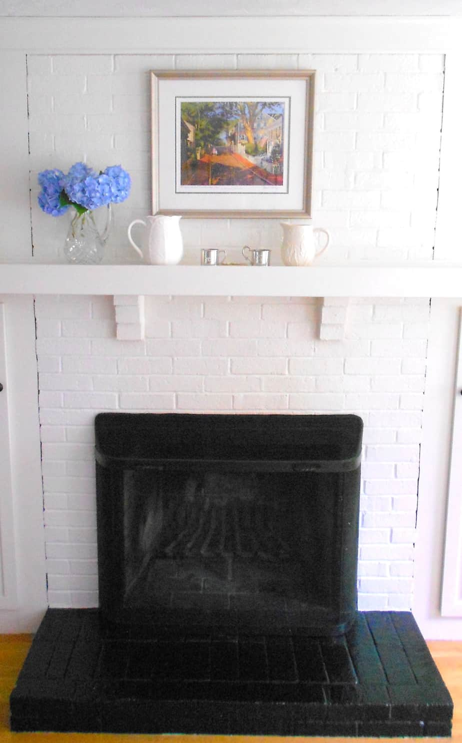 An outdated painted brick fireplace before a dramatic makeover.