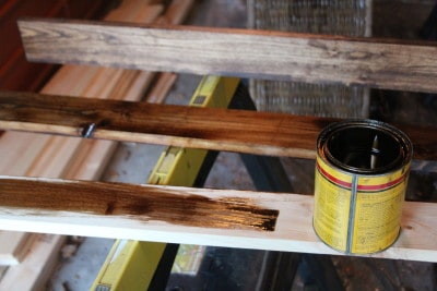 Select pine boards are stained with a mixture of Minwax Jacobean and Red Mahogany, then distressed with a palm sander to give the wood a worn look similar to a well loved baseball glove.