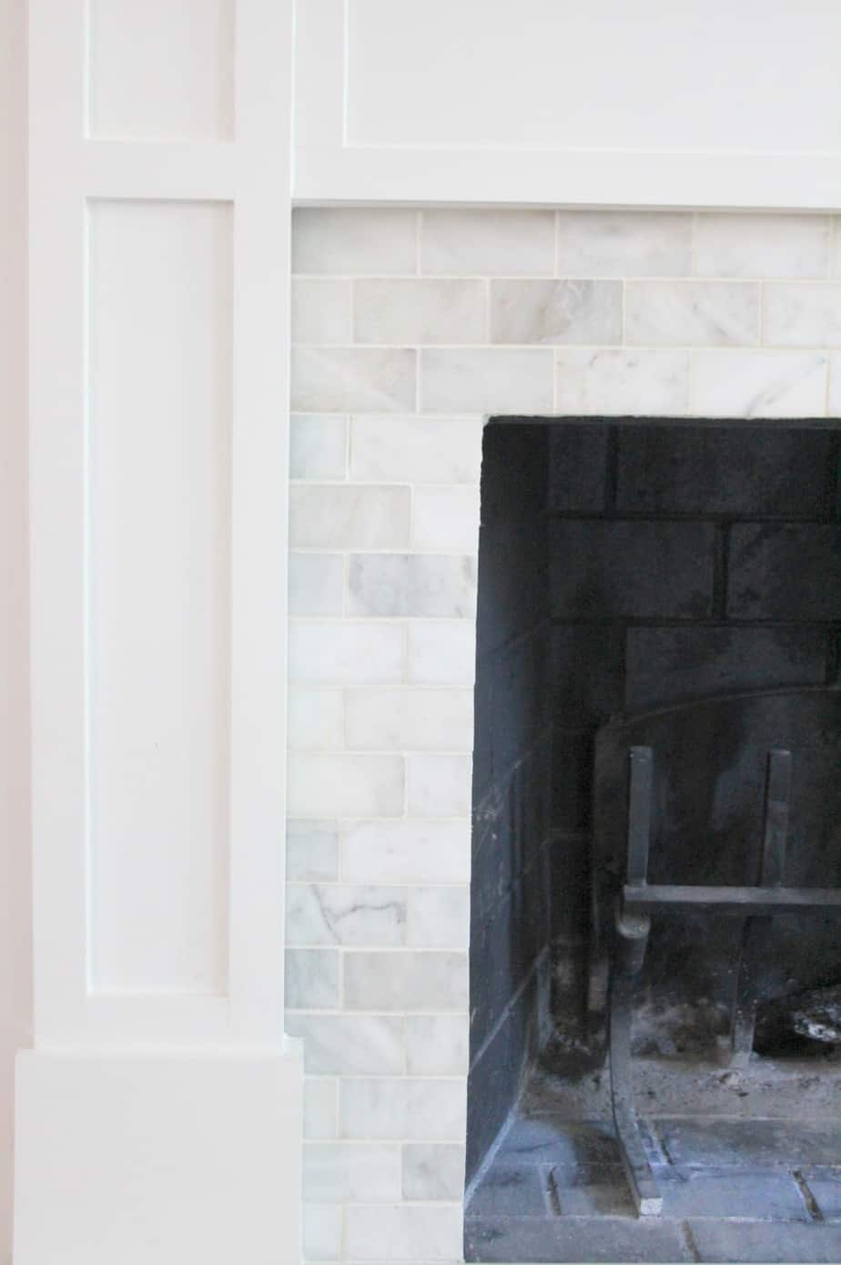 An outdated brick fireplace is resurfaced with marble tiles.