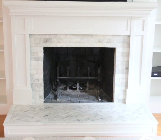 An outdated fireplace is resurfaced with marble tiling.
