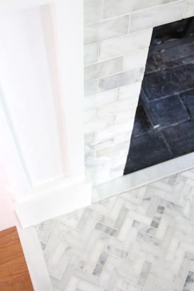 An outdated fireplace is given a facelift with marble tiling on the hearth and surround.
