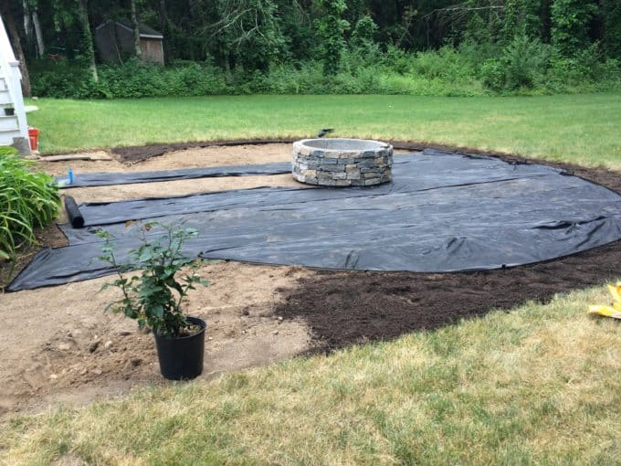 Install landscape fabric to inhibit weed growth on a pea stone patio or path.