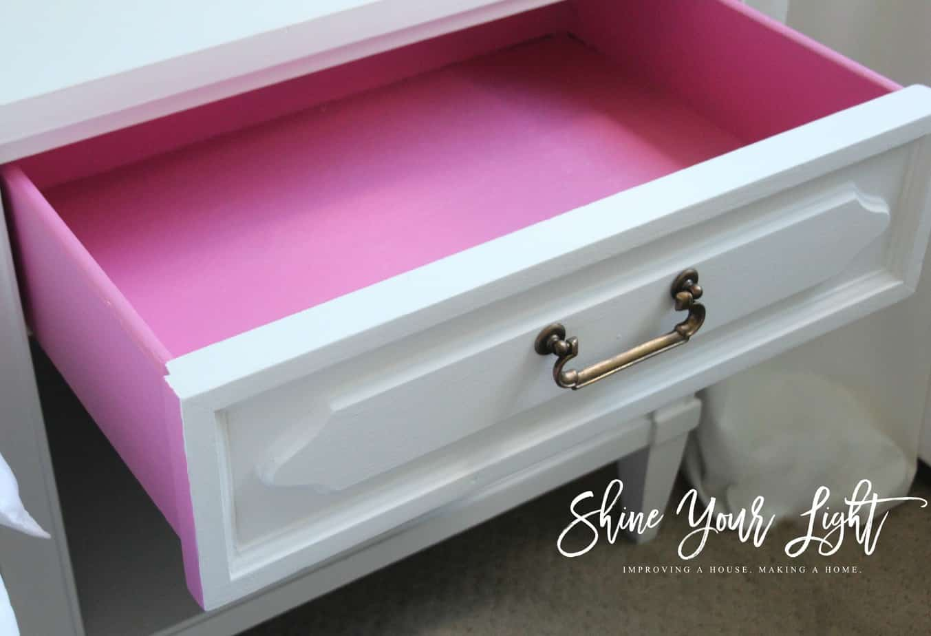 The inside of this thrifted bedside table is painted a fun hot pink.