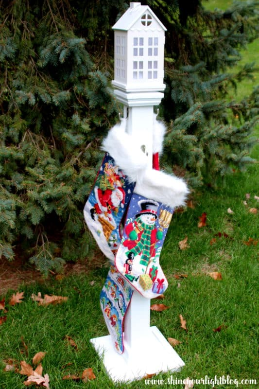 A post for hanging Christmas stockings, topped with a lantern with a battery operated light.