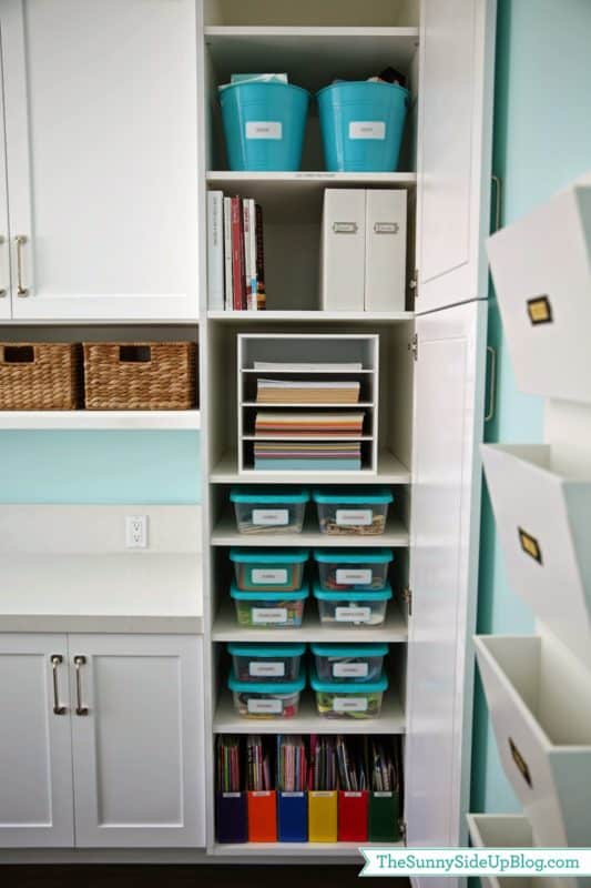 Craft and school supplies are organized neatly into cabinets