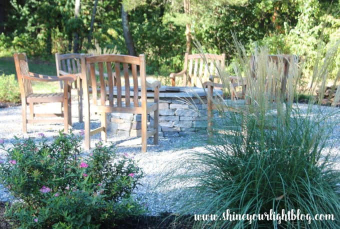 A DIY pea stone patio with stone fire pit.
