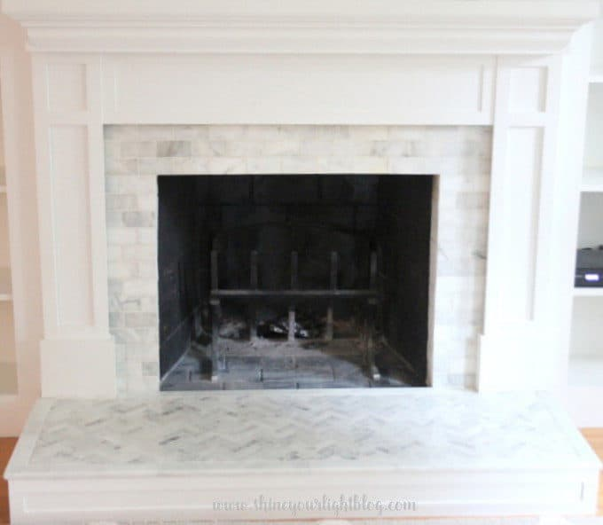 A brick fireplace is updated with marble tiling.
