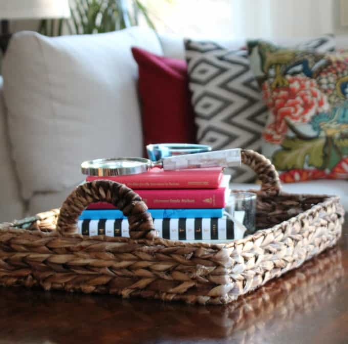 Wicker tray with handles found at a thrift store corals books on a coffee table.