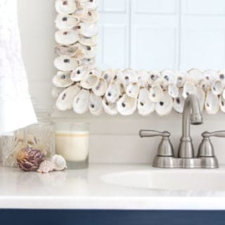 A blue and white color scheme, oyster shell mirror and beach photography give this bathroom a coastal vibe.