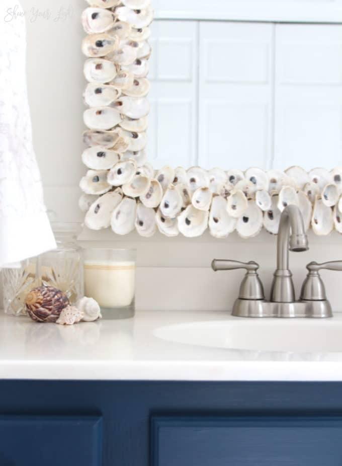 Updated 80s bathroom with marble herringbone tile flooring, navy painted vanity and coastal touches.