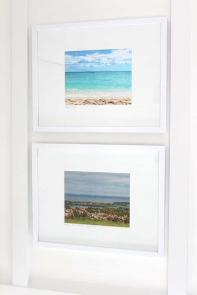 Travel photos enlarged and framed for a coastal-inspired bathroom.