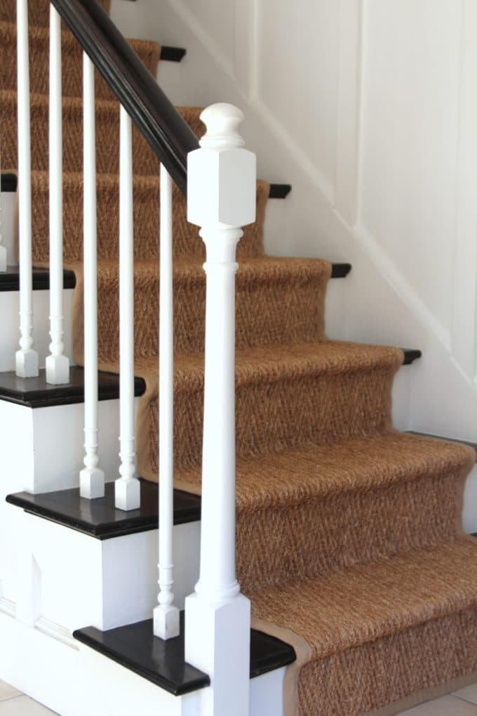 An orange oak staircase with stained carpets gets a makeover with ebony stain and a seagrass runner.