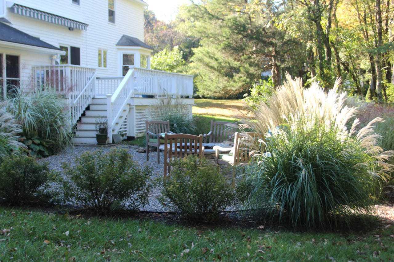A garden border around a pea stone patio includes ornamental grasses, hosta and tiger lilies.