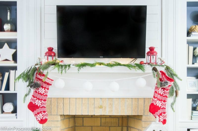 A Christmas fireplace with a TV over the mantle at Wife In Progress.