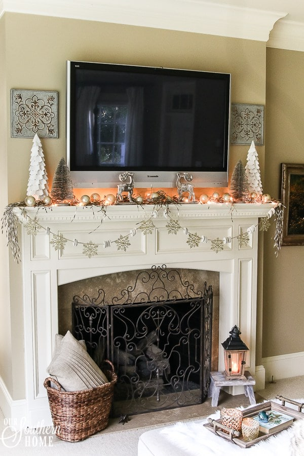 A Christmas fireplace with a TV over the mantle by Our Southern Home.