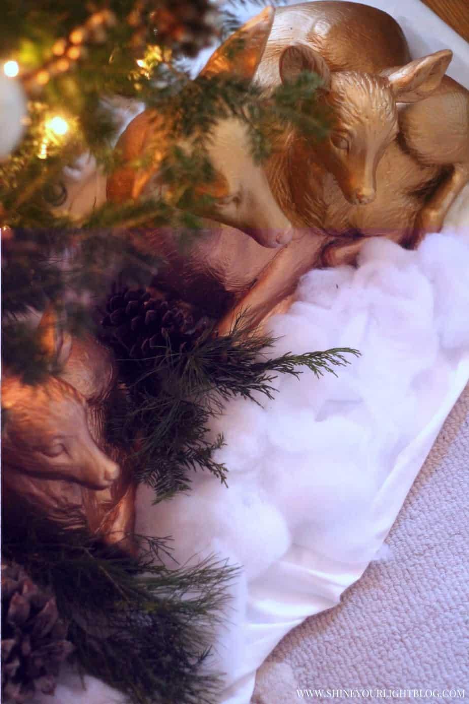 Golden deer nestled under a woodland Christmas tree