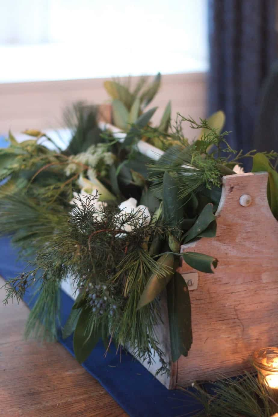 A simple centerpiece of fresh greens and flowers tucked into vases inside a wooden toolbox.