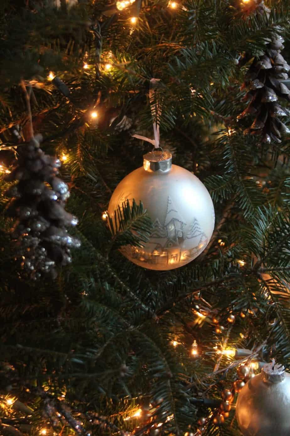A woodland Christmas tree with tree lights illuminating house ornament