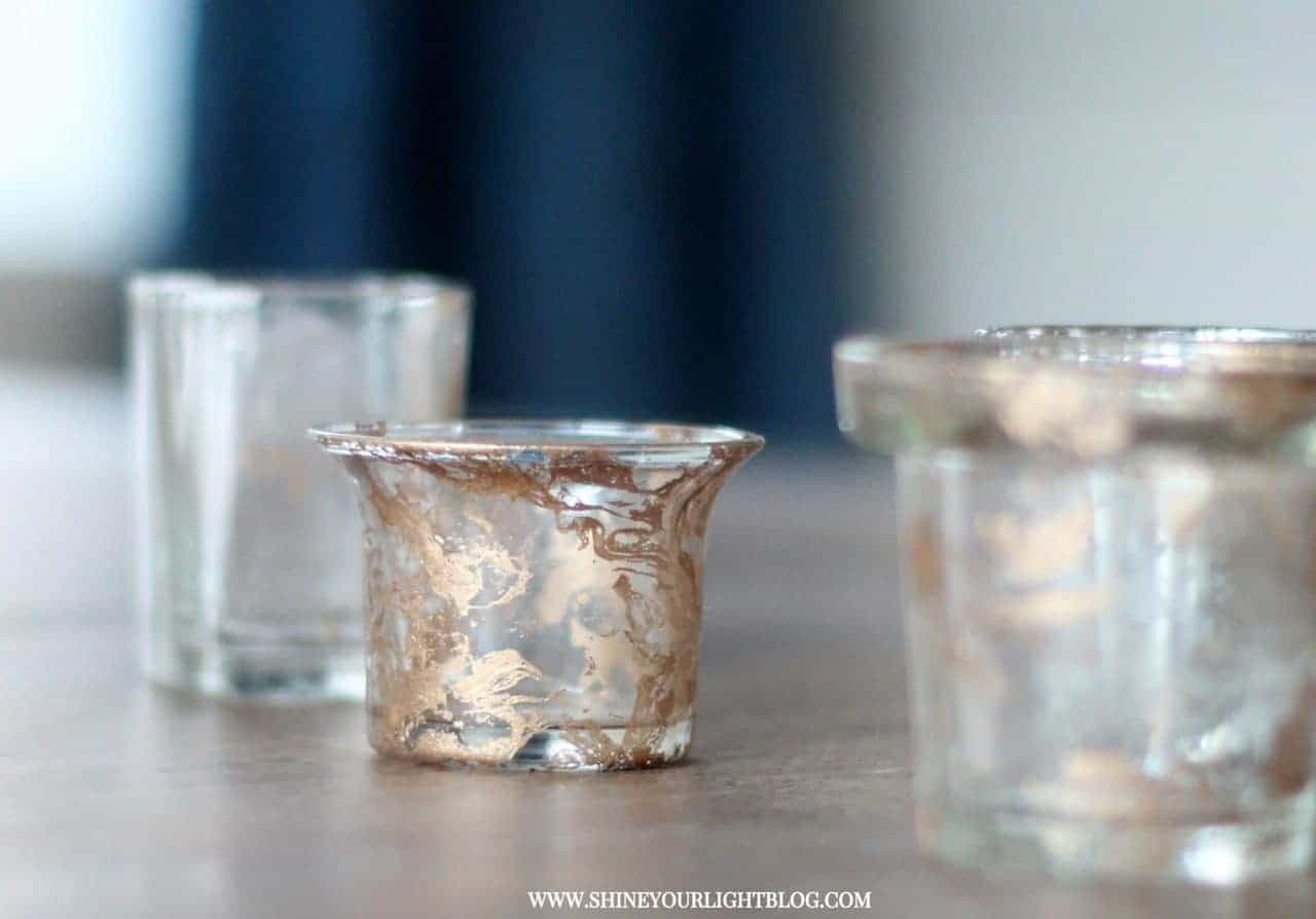 Gold marbled votive holders have a finish that is achieved by misting spray paint onto water and dipping the piece.