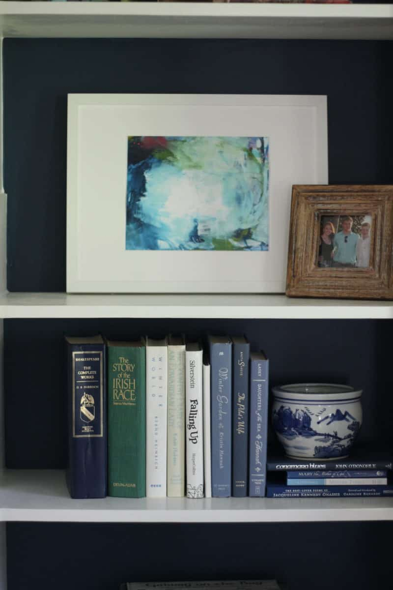 Abstract art print by Amira Rahim in bookcases flanking a fireplace.