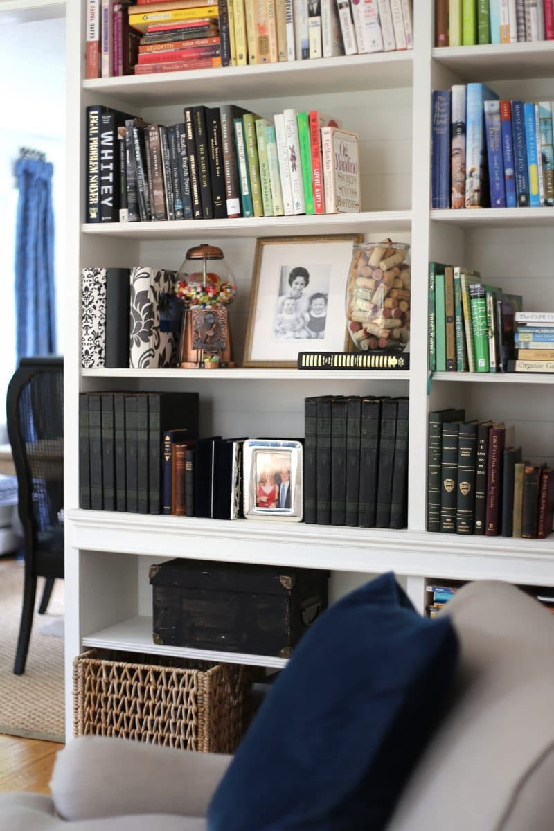 Built in bookcases with old and new books and black and white photos.