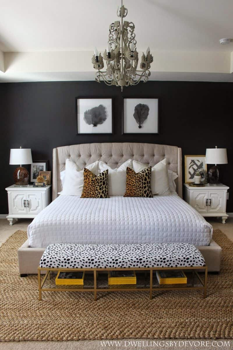 A master bedroom with black bedroom walls by Dwellings By Devore.
