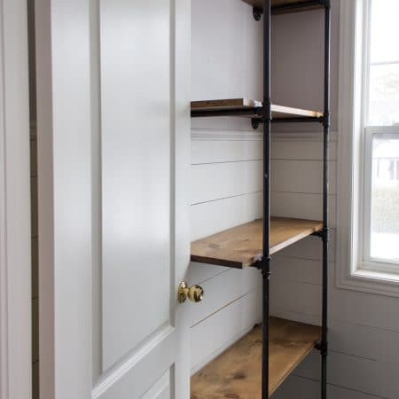Pipe shelves with stained wood installed on shiplapped walls.