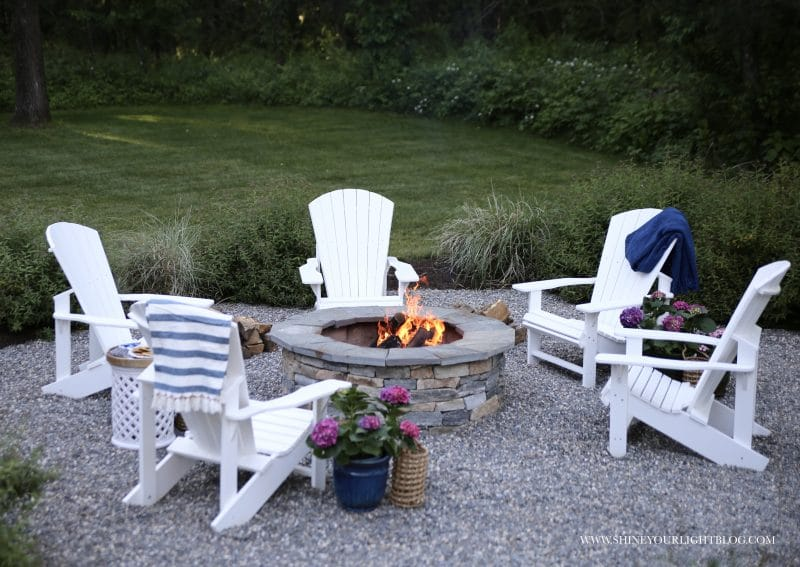 DIY pea stone patio with Adirondack chairs around a fire pit