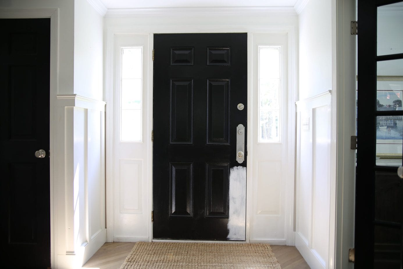 Black doors in white foyer
